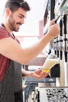Smiling young male bartender pours fresh light beer from tap