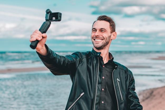 Улыбающийся молодой мужчина-блоггер делает селфи или потоковое видео на пляже, используя камеру действия со стабилизатором камеры.
