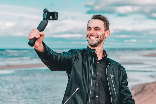 Smiling young male blogger making selfie or streaming video at the beach using action camera with gimbal camera stabilizer.