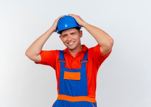 制服と安全ヘルメットを身に着けている笑顔の若い男性ビルダーは白で頭をつかんだ
