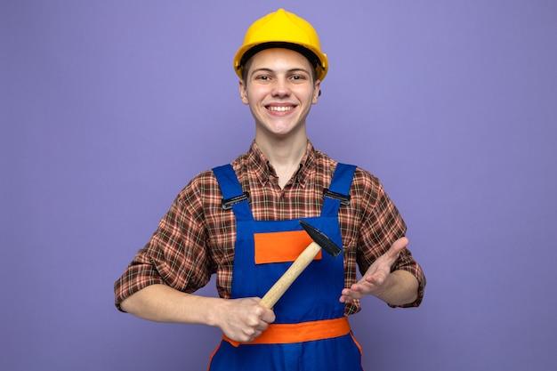 均一な保持ハンマーを身に着けている若い男性ビルダーの笑顔