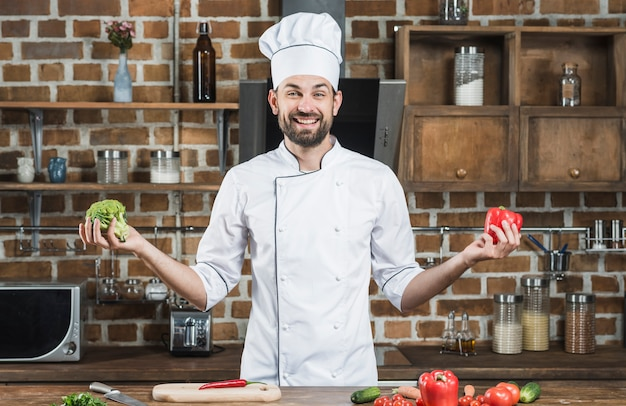 Smiling young male chef holding broccoli and red bell pepper in his hands