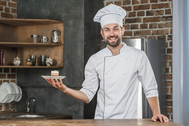 Smiling young male chef presenting dessert in the kitchen