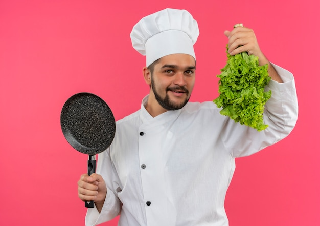 Sorridente giovane cuoco maschio in uniforme del cuoco unico che tiene padella e lattuga isolato su spazio rosa