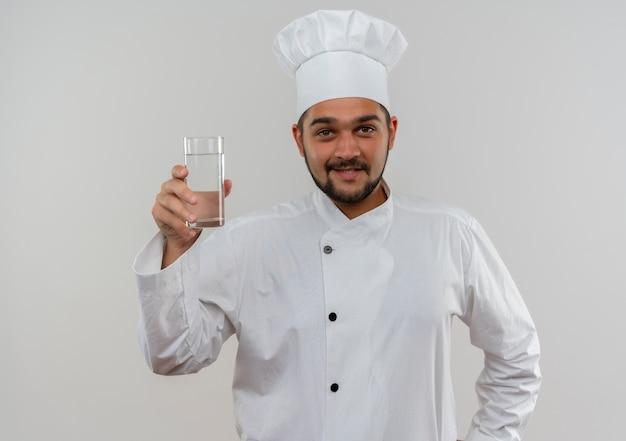 Sorridente giovane cuoco maschio in uniforme del cuoco unico che tiene bicchiere d'acqua isolato su spazio bianco