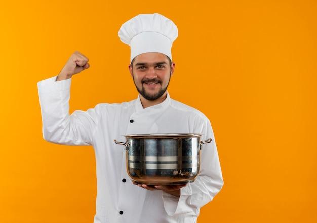 Sorridente giovane cuoco maschio in uniforme del cuoco unico che tiene pentola e gesticolando forte isolato su spazio arancione