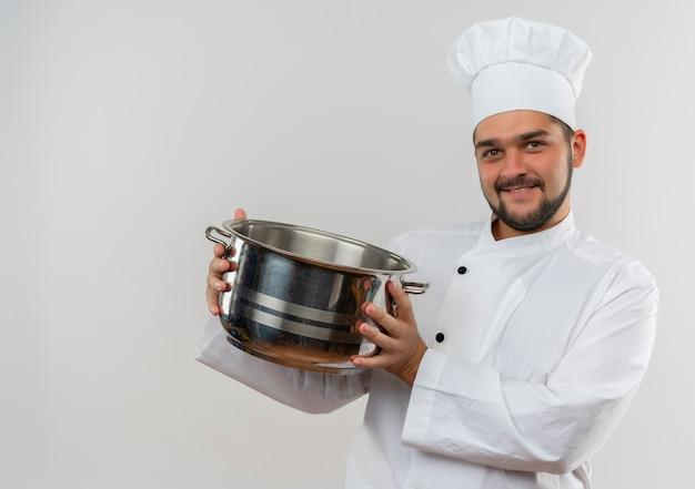Sorridente giovane cuoco maschio in uniforme del cuoco unico che tiene pentola e guardando isolato su spazio bianco