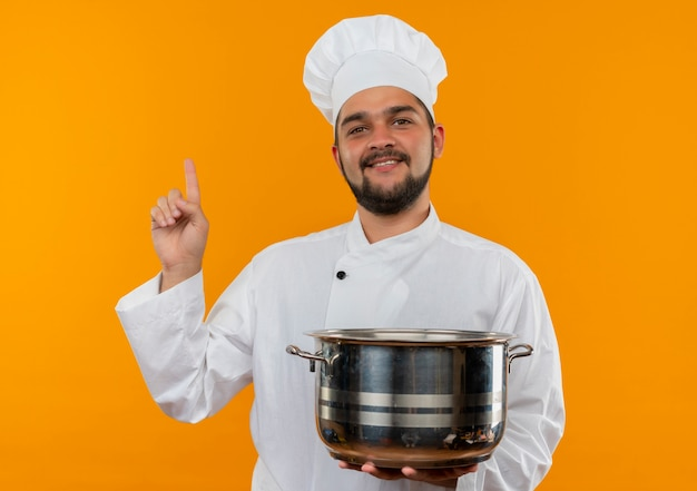 Smiling young male cook in chef uniform holding pot and looking up isolated on orange space