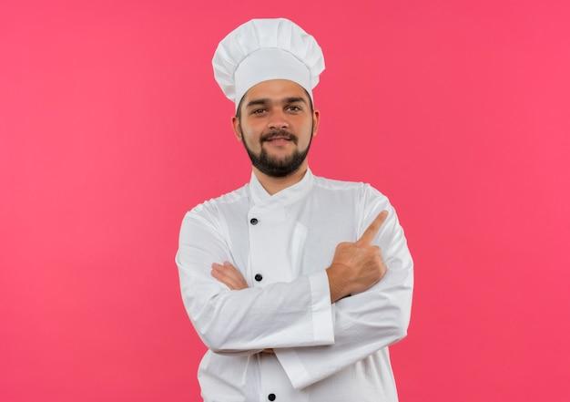 Sorridente giovane cuoco maschio in uniforme da chef in piedi con la postura chiusa e indicando il lato isolato sullo spazio rosa
