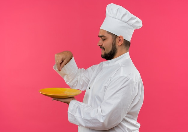 Улыбающийся молодой мужчина-повар в униформе шеф-повара держит тарелку и добавляет соль, изолированную на розовом пространстве