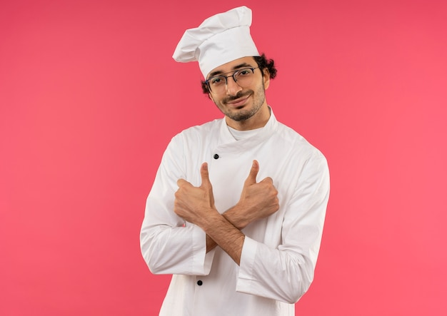 ピンクの壁に隔離されたシェフの制服と眼鏡をかけて笑顔の若い男性料理人