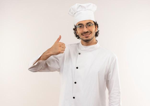 シェフの制服を着て、白い壁に隔離された彼の親指を眼鏡をかけて笑顔の若い男性料理人
