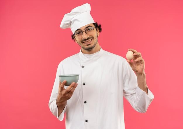 Улыбающийся молодой мужчина-повар в униформе шеф-повара и очках держит миску и яйцо, изолированные на розовой стене