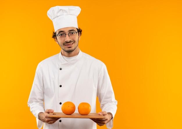 노란색 벽에 고립 된 커팅 보드에 오렌지를 들고 요리사 유니폼과 안경을 쓰고 웃는 젊은 남성 요리사