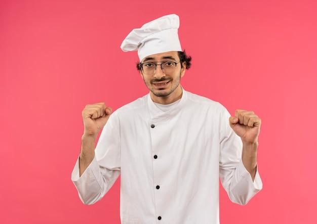 ピンクの壁に分離されたジェスチャーを示すシェフの制服と眼鏡を身に着けている若い男性料理人の笑顔