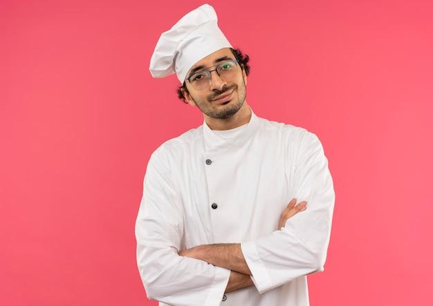 Sorridente giovane cuoco maschio che indossa l'uniforme del cuoco unico e occhiali che attraversano le mani sul rosa