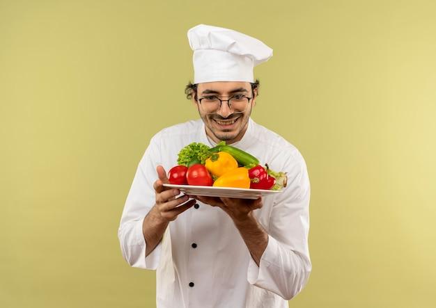 Sorridente giovane cuoco maschio che indossa l'uniforme dello chef e bicchieri tenendo e guardando le verdure sul piatto isolato sulla parete verde
