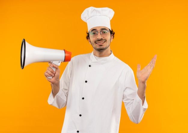 Sorridente giovane cuoco maschio che indossa l'uniforme del cuoco unico e bicchieri che tengono altoparlante e diffondere la mano isolata sulla parete gialla