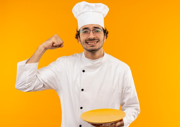 Smiling young male cook wearing chef uniform and glasses holding plate and doing strong gesture isolated on yellow wall