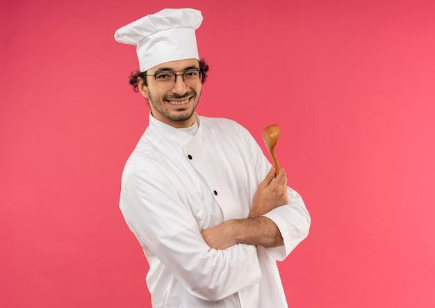 Sorridente giovane cuoco maschio che indossa l'uniforme del cuoco unico e bicchieri che tengono cucchiaio e mani incrociate isolate sulla parete rosa con lo spazio della copia