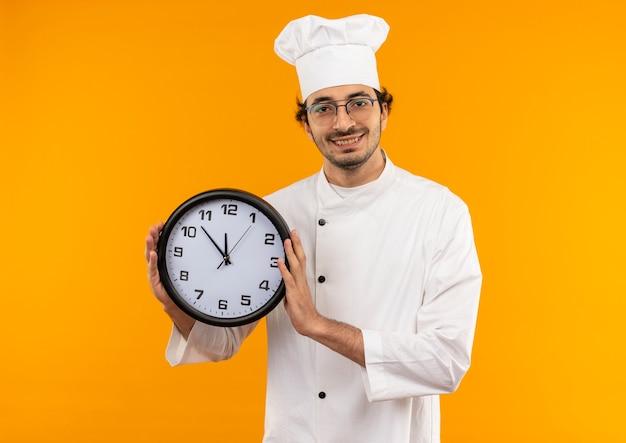Sorridente giovane cuoco maschio che indossa l'uniforme del cuoco unico e bicchieri tenendo l'orologio da parete isolato sulla parete gialla