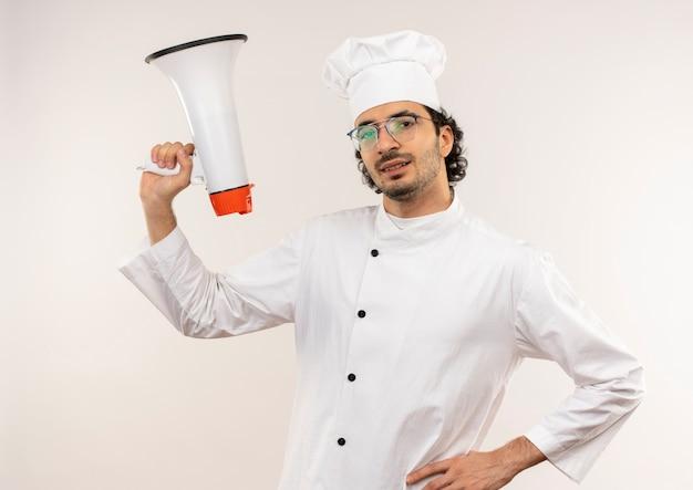Sorridente giovane cuoco maschio che indossa l'uniforme del cuoco unico e vetri che alzano altoparlante mettendo la mano sull'anca isolata sulla parete bianca
