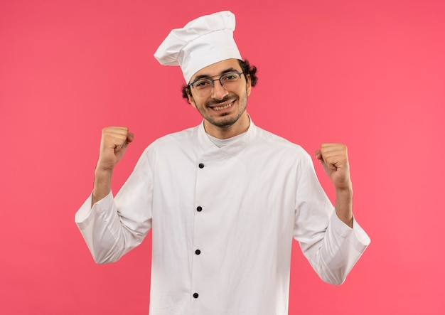 Sorridente giovane cuoco maschio indossando l'uniforme del cuoco unico e vetri che mostrano sì gesto isolato sulla parete rosa