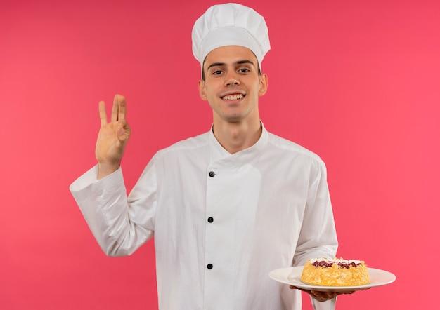 Улыбающийся молодой мужчина-повар в униформе шеф-повара держит торт на тарелке и показывает жест окей
