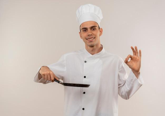 Улыбающийся молодой мужчина-повар в униформе шеф-повара держит сковороду и показывает жест окей