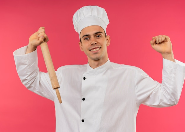 Smiling young male cook wearing chef uniform holding rolling pin doing strong gesture
