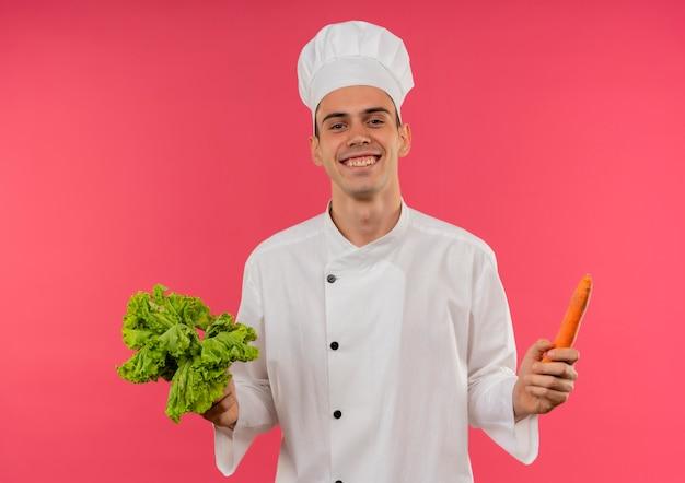 サラダとニンジンを保持しているシェフの制服を着て笑顔の若い男性料理人