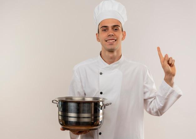 鍋を持っているシェフの制服を着て笑顔の若い男性料理人がコピースペースで指を上に向ける