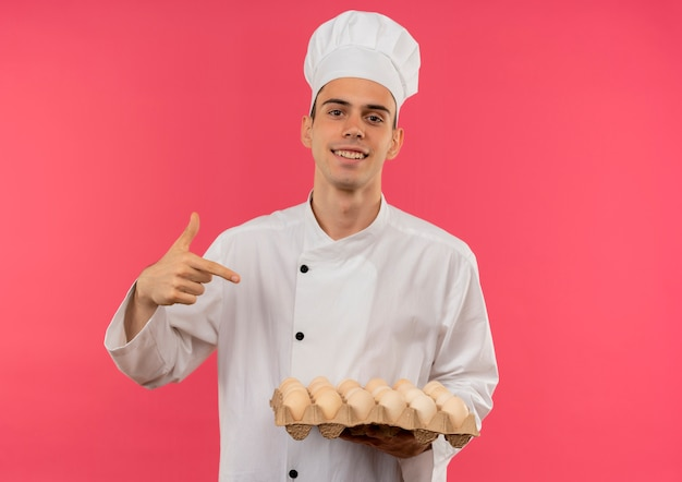 Smiling young male cook wearing chef uniform points finger to batch of eggs in his hand with copy space