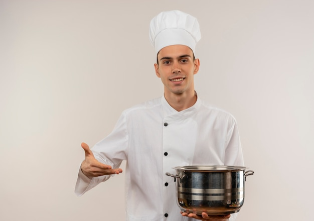 Smiling young male cook wearing chef uniform showing saucepan in his hand with copy space
