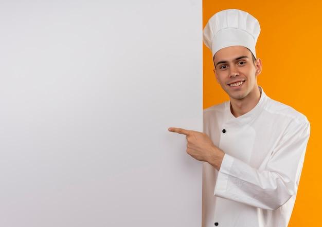 웃는 젊은 남성 멋진 입고 요리사 유니폼 포인트 복사 공간이 흰 벽에 손가락