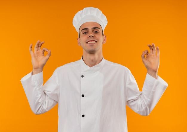 Улыбающийся молодой мужчина круто в форме шеф-повара показывает хорошие жесты