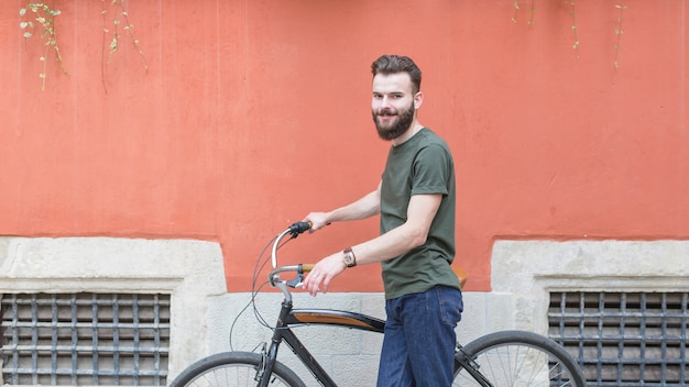 Smiling young male cyclist with bicycle in front of wall