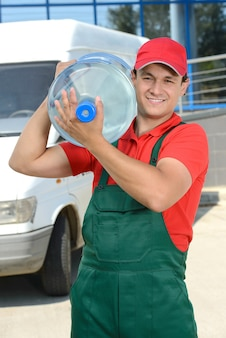 Smiling young male delivery courier man with water.
