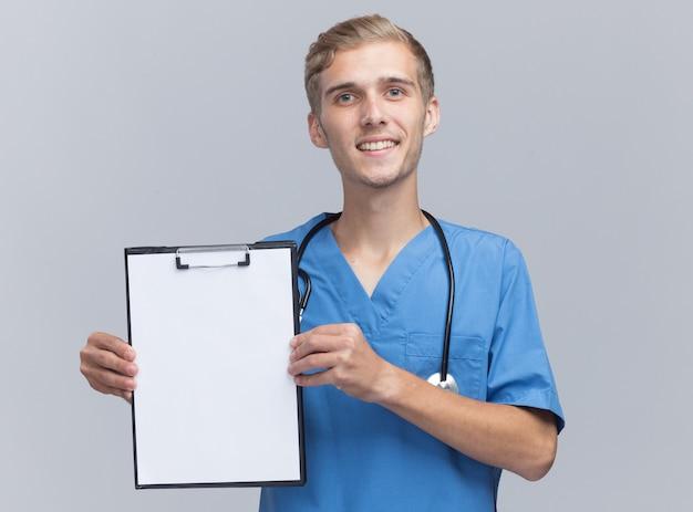 Sorridente giovane medico maschio che indossa l'uniforme del medico con lo stetoscopio che tiene appunti isolato sulla parete bianca