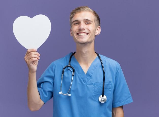 Sorridente giovane medico maschio che indossa l'uniforme del medico con lo stetoscopio che tiene la scatola a forma di cuore isolata sulla parete blu