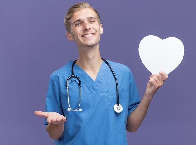 Sorridente giovane medico maschio che indossa l'uniforme del medico con lo stetoscopio che tiene i punti della scatola di forma del cuore con la mano alla macchina fotografica isolata sulla parete blu