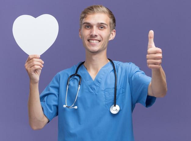 Sorridente giovane medico maschio che indossa l'uniforme del medico con lo stetoscopio che tiene la scatola a forma di cuore che mostra il pollice in su isolato sulla parete blu