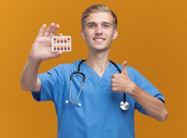 청진 기 들고 약을 들고 의사 유니폼을 입고 웃는 젊은 남성 의사는 오렌지 벽에 고립 엄지 손가락을 보여주는