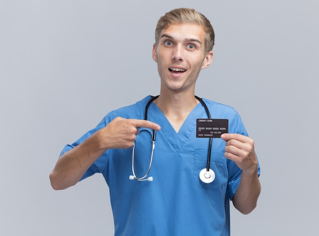 Smiling young male doctor wearing doctor uniform with stethoscope holding and points at credit card isolated on white wall