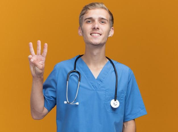 오렌지 벽에 고립 된 3을 보여주는 청진 기와 의사 유니폼을 입고 웃는 젊은 남성 의사
