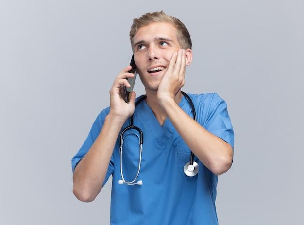 청진기와 의사 유니폼을 입고 웃는 젊은 남성 의사는 흰 벽에 고립 된 뺨에 손을 넣어 전화에 말한다