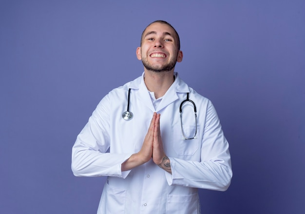 紫色の壁に隔離された祈りのジェスチャーで手を入れて彼の首に医療ローブと聴診器を身に着けている若い男性医師の笑顔