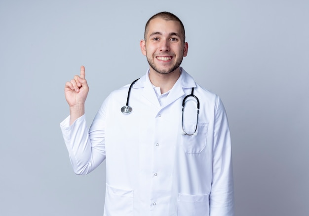 白い壁に隔離された指を上げる彼の首の周りに医療ローブと聴診器を身に着けている若い男性医師の笑顔