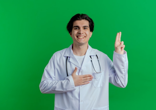 コピースペースと緑の壁に分離された約束のジェスチャーを行う医療ローブと聴診器を身に着けている若い男性医師の笑顔