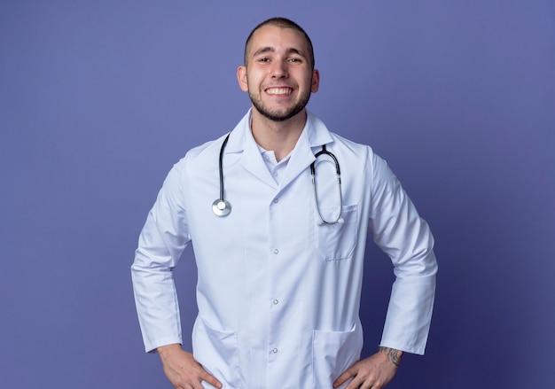 보라색 벽에 고립 된 허리에 손을 댔을 의료 가운과 청진기를 입고 웃는 젊은 남성 의사